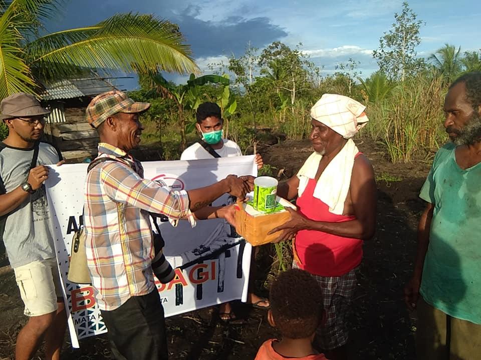 ketua komunitas Asmat Fotografi, Wilhelmus Kolyaan saat memberikan bantuan bibit kepada petani lokal.